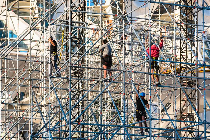 Valencia, Spain - May 28, 2019: Workers assembling a stage for a concert, hanging from the metal bars of the structure with. Harnesses and increase their job stock photography