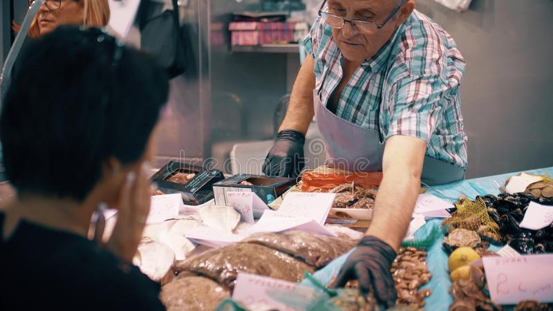 VALENCIA, SPAIN - SEPTEMBER 22, 2018. Customer and vendor at seafood stall in famous Mercado Central or Central Market. VALENCIA, SPAIN - SEPTEMBER 22, 2018 stock photo