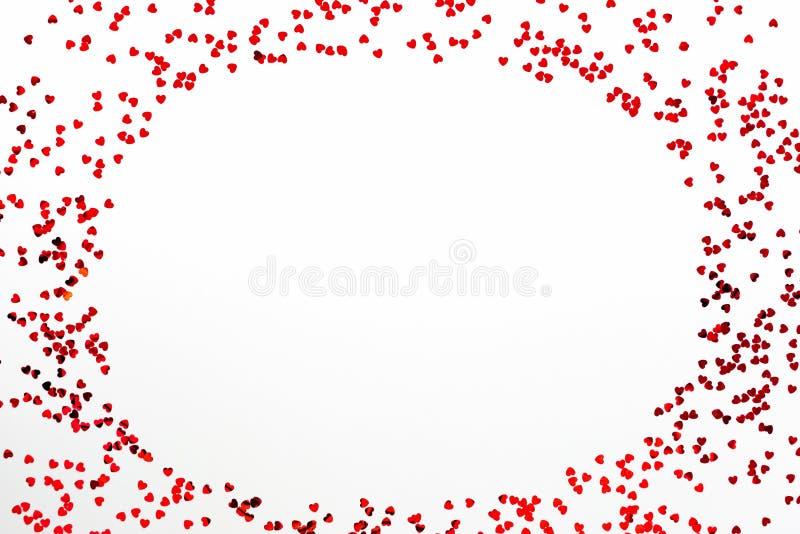 Valentijnsdag-achtergrond - een frame van verspreid hartvormig confetti boven witte achtergrond royalty-vrije stock foto's