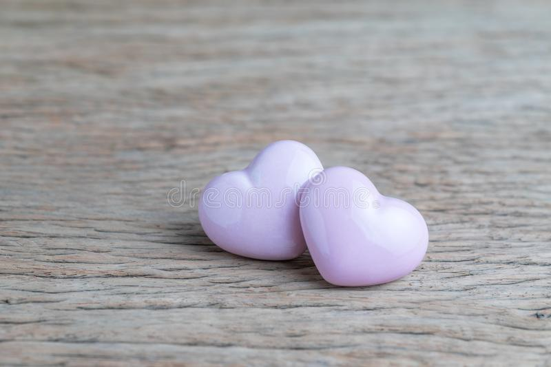 Valentijnskaarten of huwelijksachtergrond, 2 roze hartvormen op houten stock fotografie