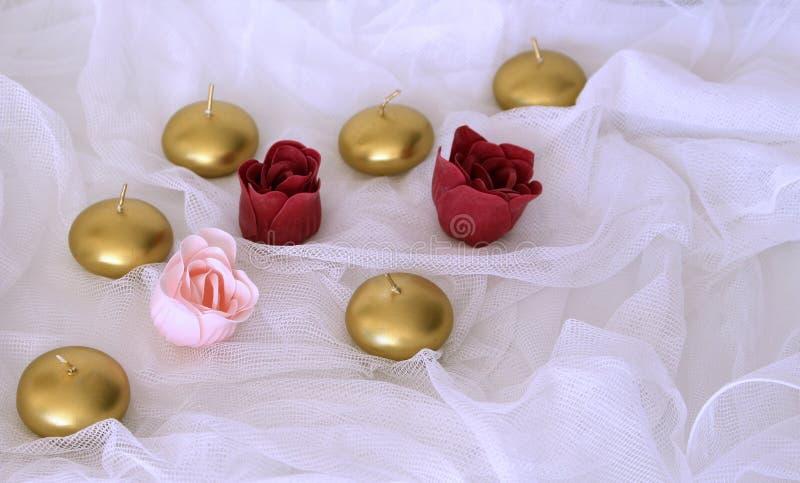 Valentijnskaartendag of Huwelijk Valentine Gift De gouden kaarsen en namen bloemen op witte satijnachtergrond toe Mooi Valentine stock afbeelding