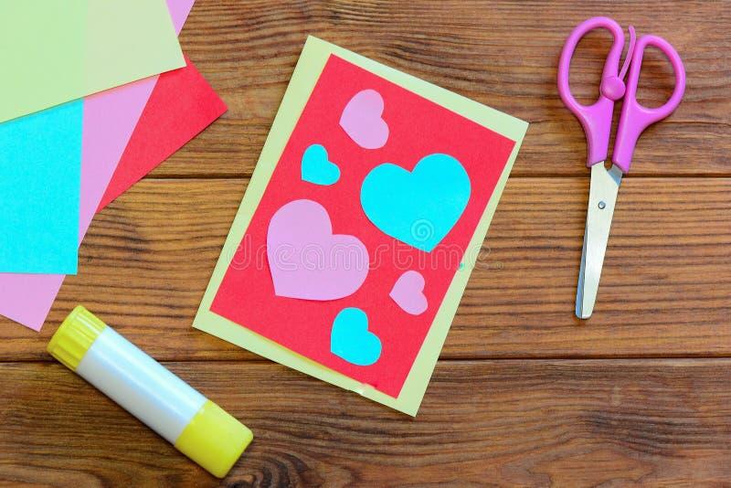 Valentijnskaartendag of van de Moedersdag prentbriefkaar met roze en blauwe harten De schaar, lijmstok, kleurde document geplaats royalty-vrije stock afbeelding