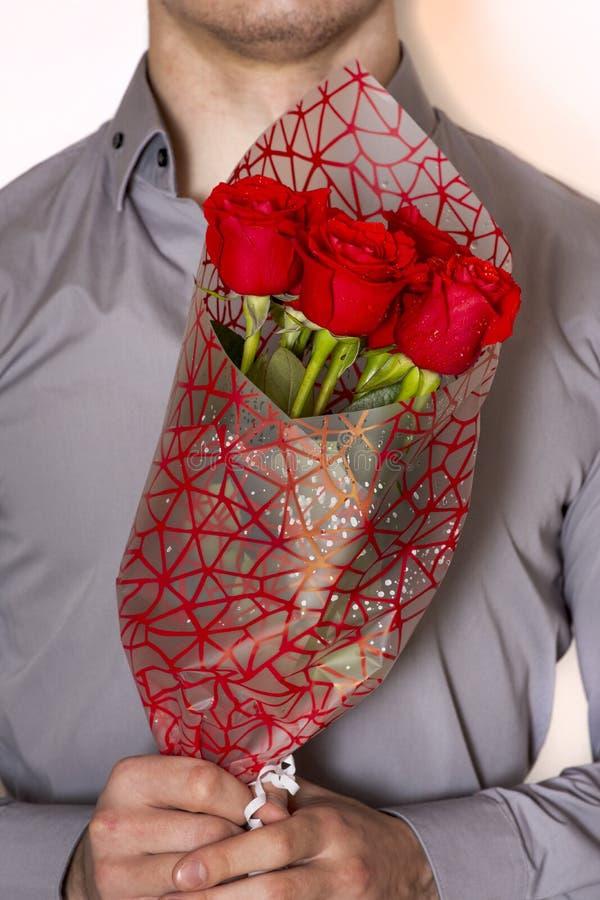 Valentijnskaartendag of voorstel Jonge gelukkige knappe mens die grote bos van rode rozen in zijn hand op grijze achtergrond houd stock fotografie