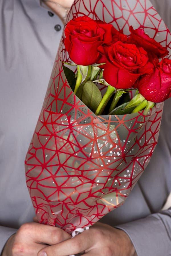 Valentijnskaartendag of voorstel Jonge gelukkige knappe mens die grote bos van rode rozen in zijn hand op grijze achtergrond houd royalty-vrije stock foto