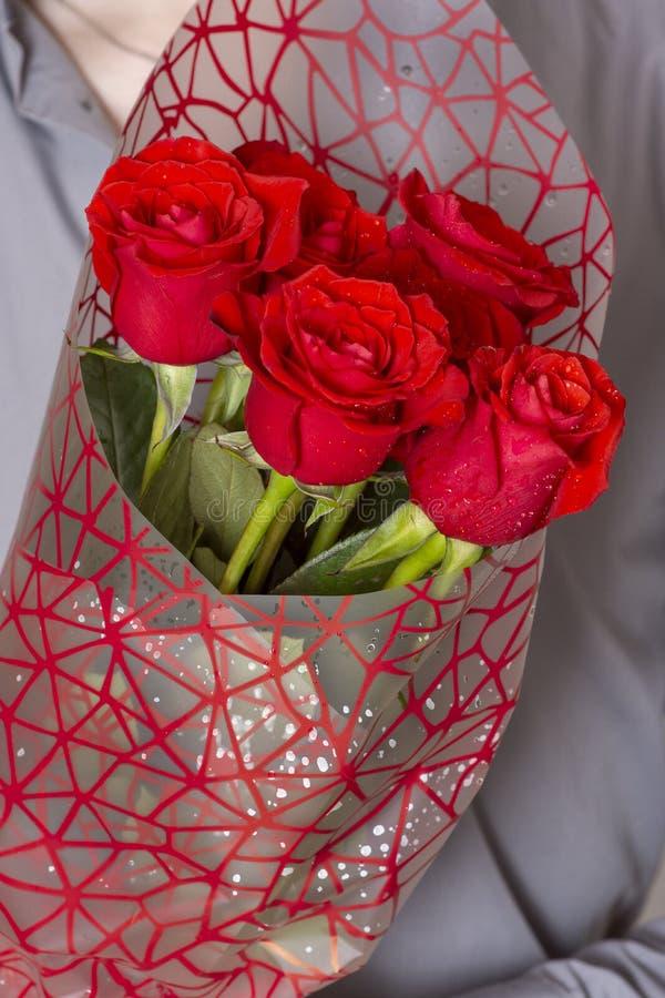 Valentijnskaartendag of voorstel Jonge gelukkige knappe mens die grote bos van rode rozen in zijn hand op grijze achtergrond houd stock afbeelding