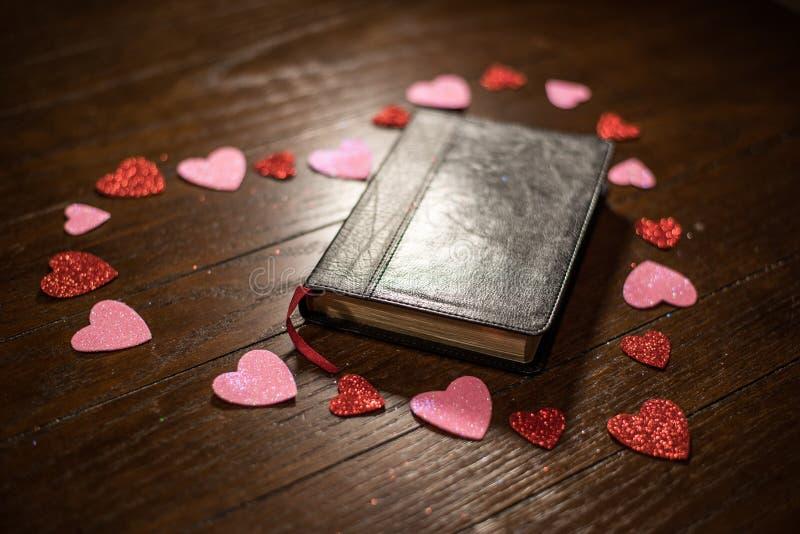 Valentijnskaartenhart en bijbel op houten lijst royalty-vrije stock afbeelding