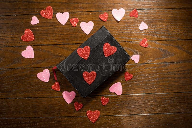 Valentijnskaartenhart en bijbel op houten lijst stock fotografie