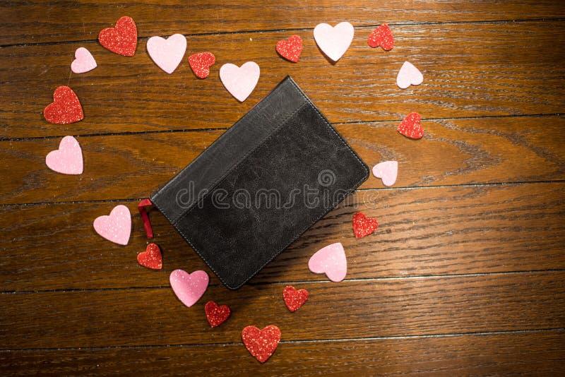 Valentijnskaartenhart en bijbel op houten lijst royalty-vrije stock fotografie