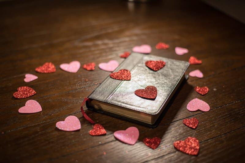 Valentijnskaartenhart en bijbel op houten lijst stock foto