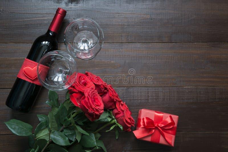 Valentijnskaartenkaart met romantische rode rozen, wijnfles, hart en rood giftvakje op houten lijst Hoogste mening met ruimte Vla stock fotografie