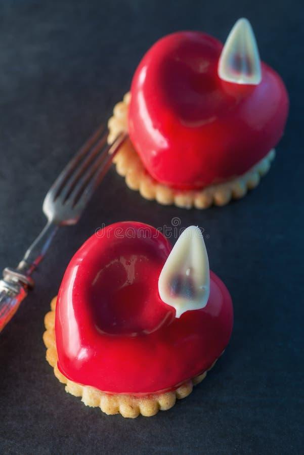Valentin bakar ihop med hjärtaform med metallgaffeln på svart backgrount, produktfotografi för bakelser royaltyfri foto
