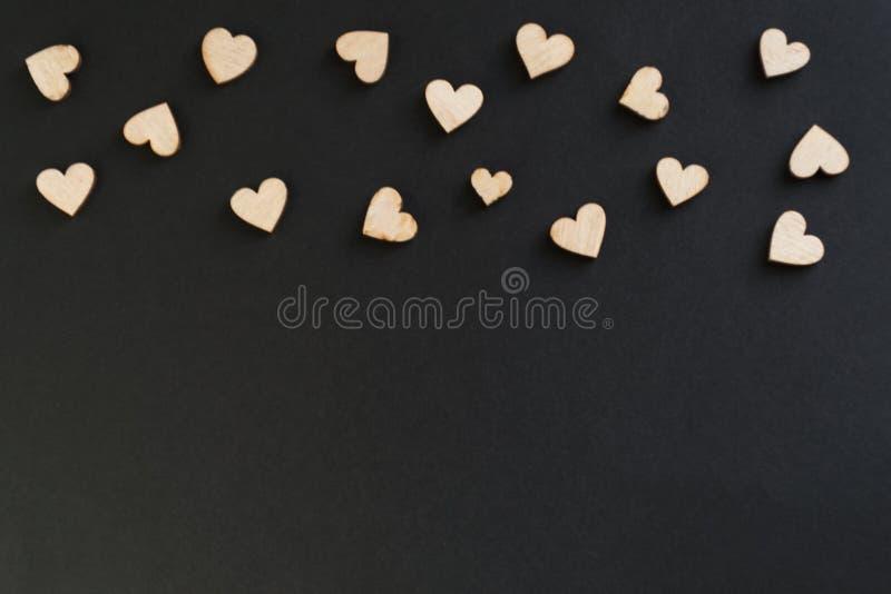 Valentin bakgrund för dagsvart med mycket trähjärtor på ett kritabräde, på en svart bakgrund Det finns ett ställe för text royaltyfri bild
