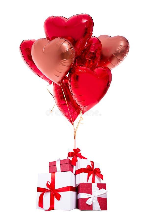 Valentin dag eller födelsedagbegrepp - gåvaaskar med röda ballonger som isoleras på vit arkivfoton