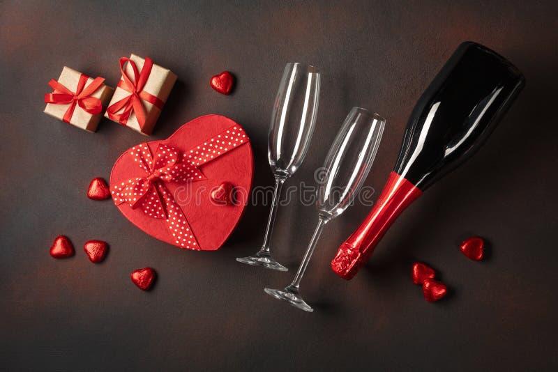 Valentin dag med en flaska av champagneexponeringsglas av choklader och gåvor Bästa sikt med kopieringsutrymme arkivfoton