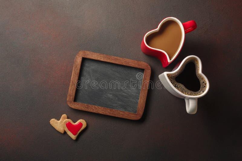 Valentin dag med gåvor, enformad ask, koppar kaffe, hjärta-formade kakor, makron och en svart tavla Bästa sikt med royaltyfri fotografi