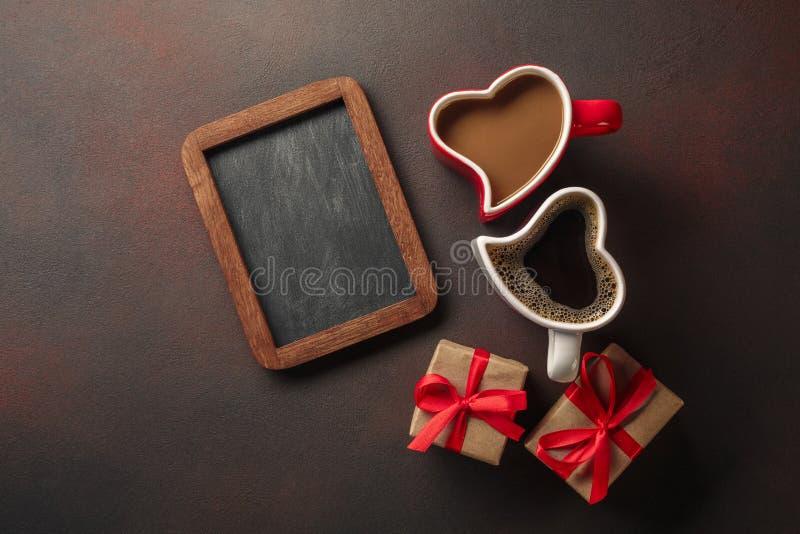 Valentin dag med gåvor, enformad ask, koppar kaffe, hjärta-formade kakor, makron och en svart tavla Bästa sikt med arkivfoto