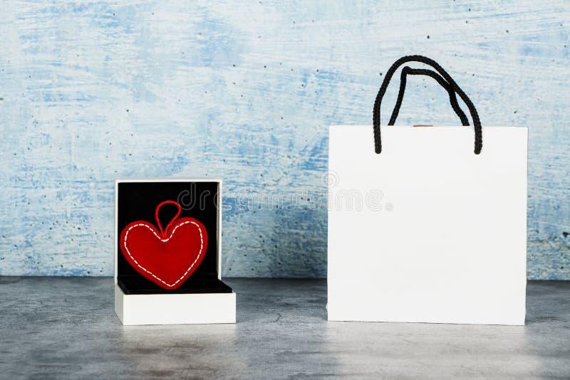 Valentin dagbakgrund med en hjärta i en gåvaask på en blå bakgrund placera text Orientering för valentin dag fotografering för bildbyråer