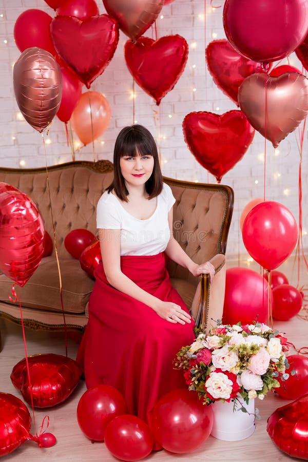 Valentin dagbegrepp - full längdstående av den unga kvinnan som sitter på tappningsoffan med röda hjärta-formade ballonger arkivfoton