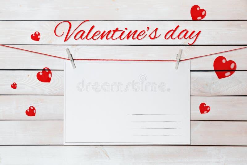 Valentin dagbokstäver och vykort på röda trådar som omges av hjärtor på trävit bakgrund fotografering för bildbyråer