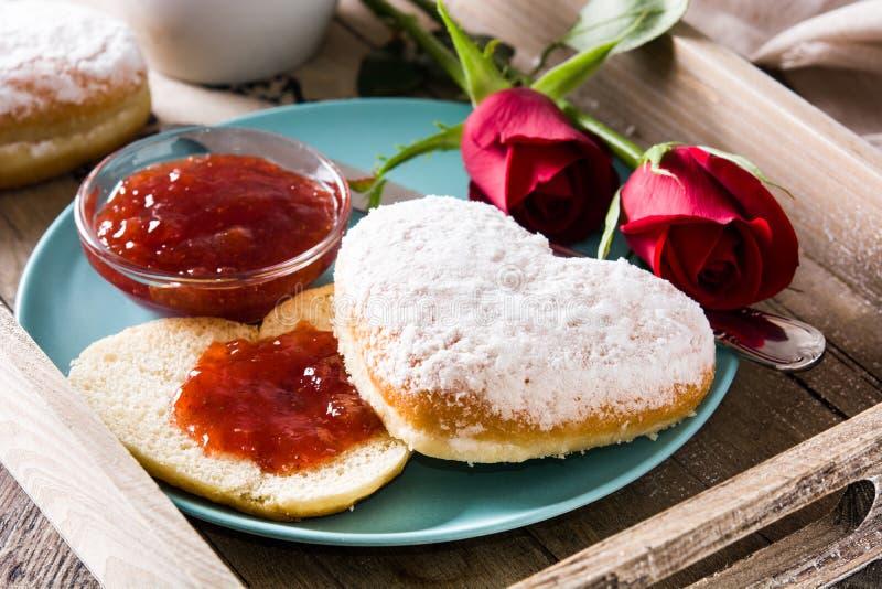 Valentin dagfrukost med kaffe, denformade bullen, bärdriftstopp och rosor arkivbilder