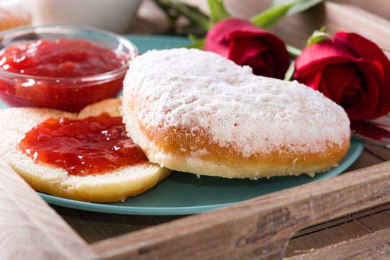 Valentin dagfrukost med kaffe, denformade bullen, bärdriftstopp och rosor royaltyfria bilder