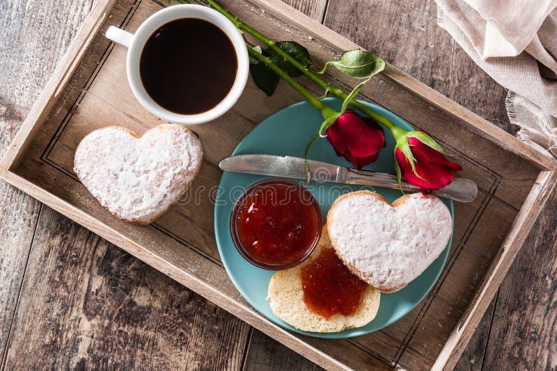 Valentin dagfrukost med kaffe, denformade bullen, bärdriftstopp och rosor arkivfoton