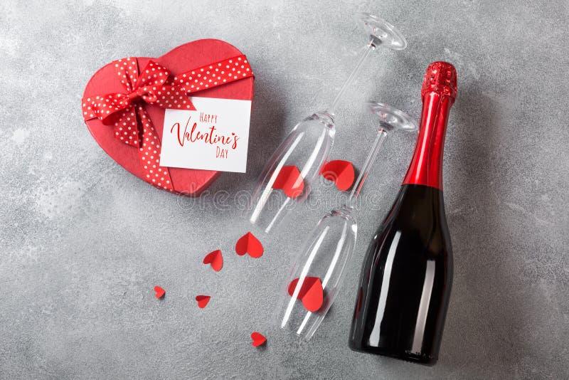 Valentin dagkort med en flaska av champagne, exponeringsglas med en ask av choklader i formen av en hjärta Bästa sikt med utrymme arkivfoton