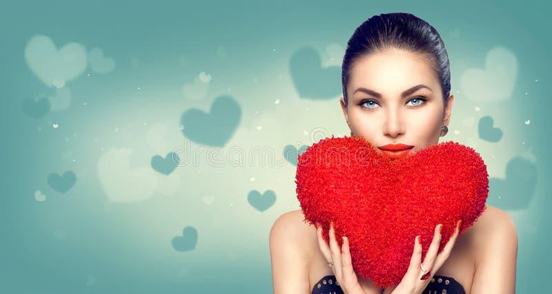 valentin för dag s Den sexiga flickan med hjärta formade den fluffiga röda kudden royaltyfria bilder