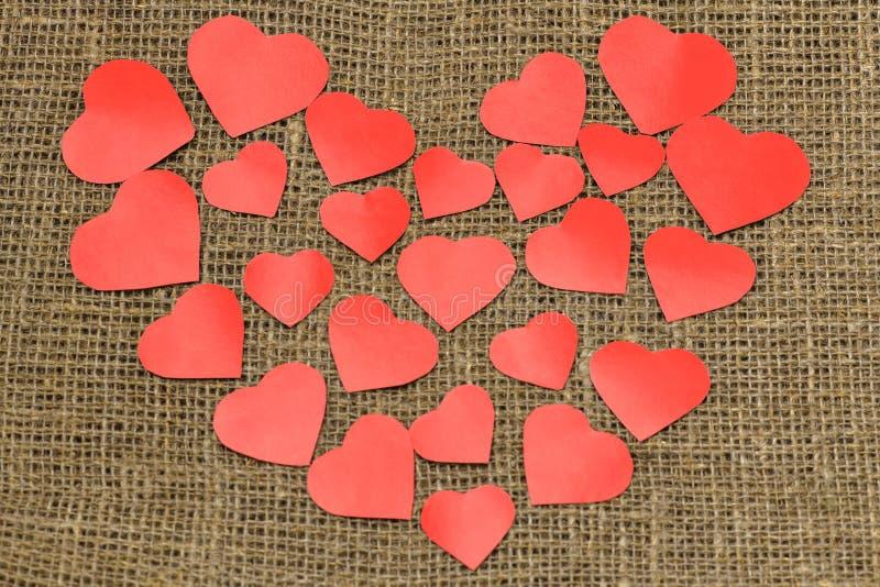 valentin för dag s En stor röd hjärta från små hjärtor ligger på en brun påse arkivfoto