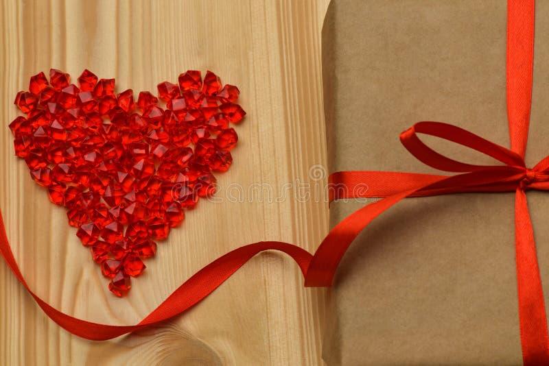 valentin för dag s En stor röd plast- exponeringsglashjärta av små kristaller ligger på ett ljust träd på den högra bruntet Kraft royaltyfri foto