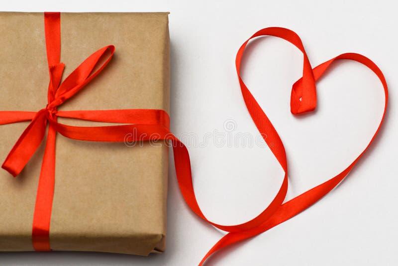 valentin för dag s Gåvaasken är på en grå bakgrund som binds med ett rött band, det röda bandet, läggas i formen av en hjärta Hjä royaltyfria bilder