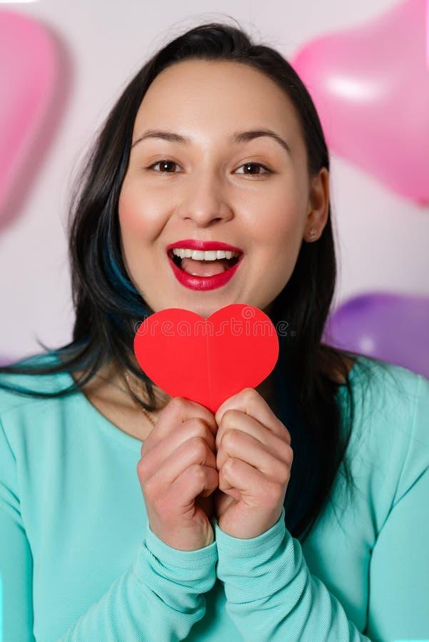 valentin för dag s Härlig ung kvinna med hjärta i henne händer Ung kvinna med röd hjärta på vit bakgrund med uppblåsbar royaltyfri foto