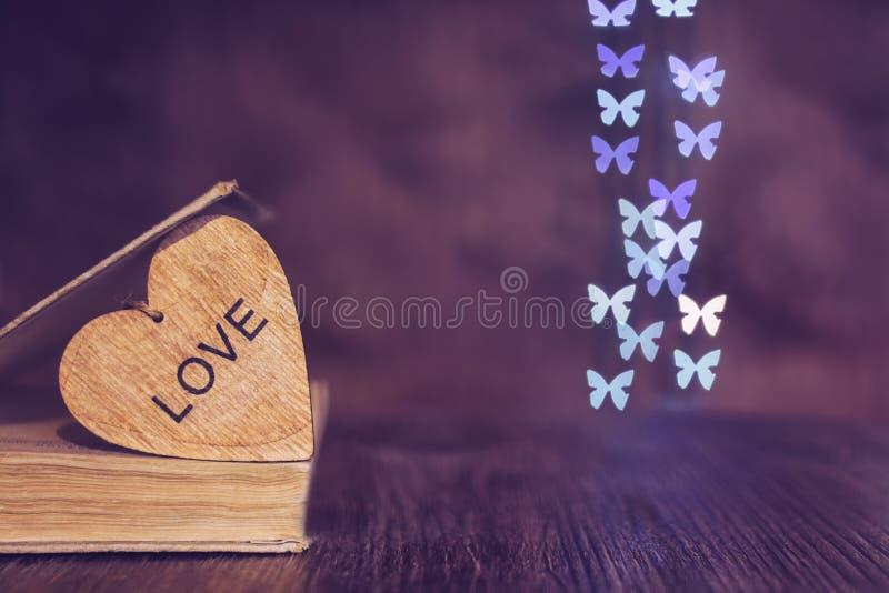 valentin för dag s Hjärtabokbokeh av fjärilar Trähjärta med ordförälskelsen royaltyfria foton