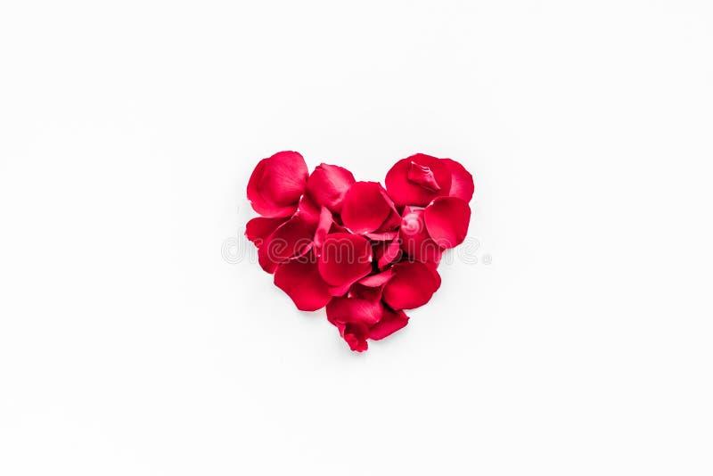 valentin för dag s Röda roskronblad i form av hjärta på vitt utrymme för kopia för bästa sikt för bakgrund royaltyfri bild