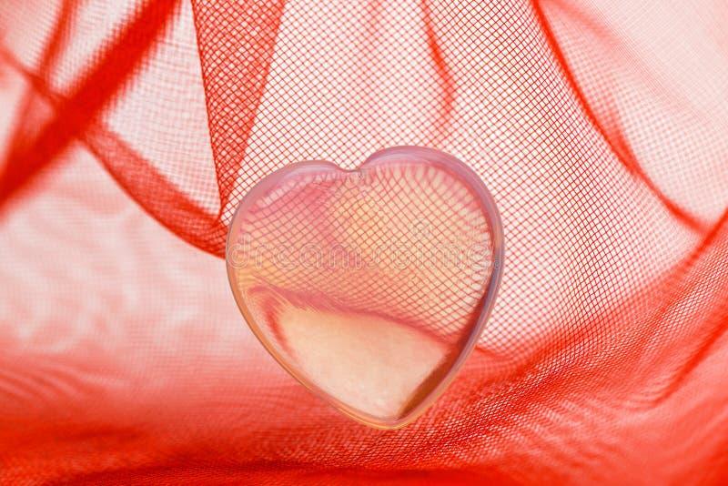valentin för dag s Små genomskinliga plast- lögner för en hjärta i ett rött genomskinligt tyg royaltyfri bild