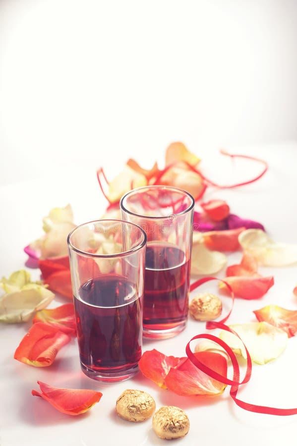 valentin för dag s Två exponeringsglas med rött vin och gåvor arkivbilder