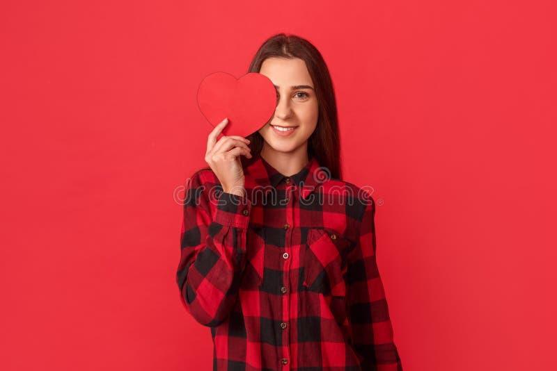 valentin för dag s Ung flickaanseende som isoleras på rött täckande öga med att le för valentinkort som är gladlynt till kameran arkivfoton