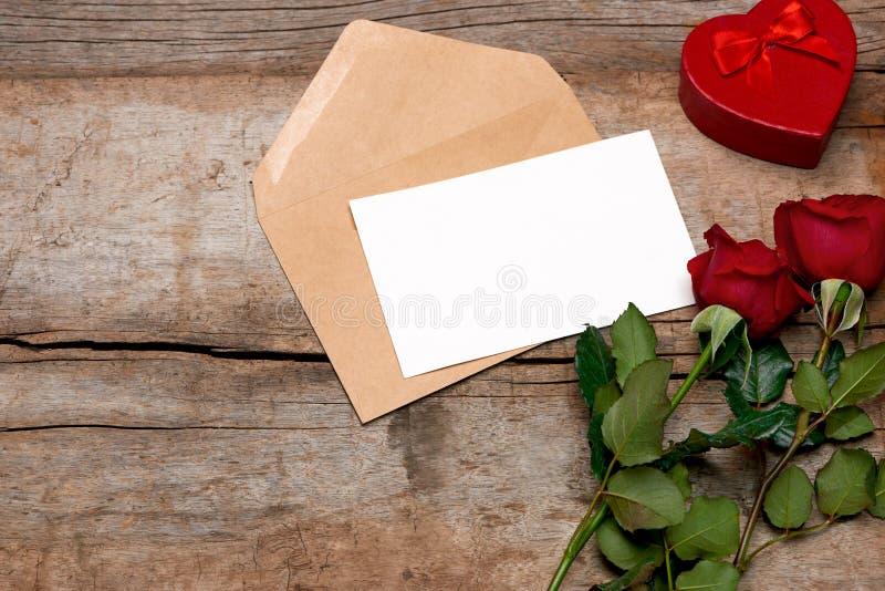 Valentin för förälskelsebokstaven steg och i kuvert på träbakgrund royaltyfri bild