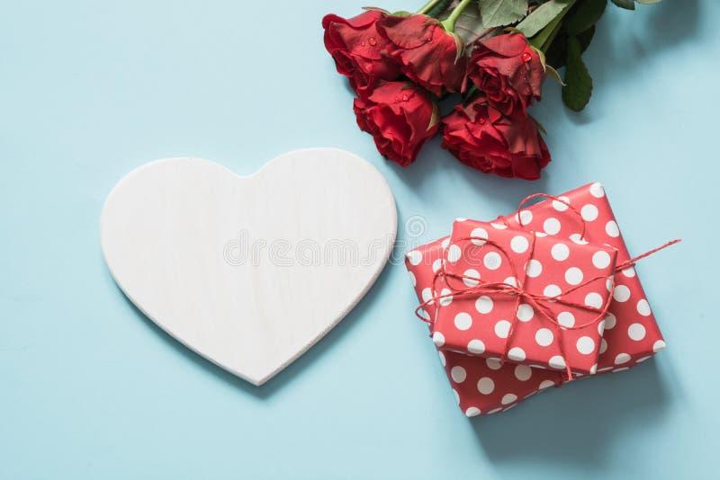 valentin för kortdaghälsning s Buketten av röda rosor och gåvan, hjärta som mellanrumet för text på blått ytbehandlar kopiera avs arkivbilder