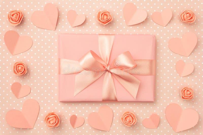 Valentin kort för daghälsning med dekorerad pappershjärta, korall eller rosa rosblommor och korallgåvaask Top beskådar Lekmanna-  royaltyfria foton