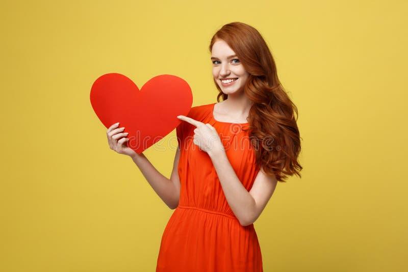 Valentin och livsstilbegrepp: Stående av en attraktiv iklädd röd klänning för ung kvinna som pekar fingret på papper royaltyfri bild