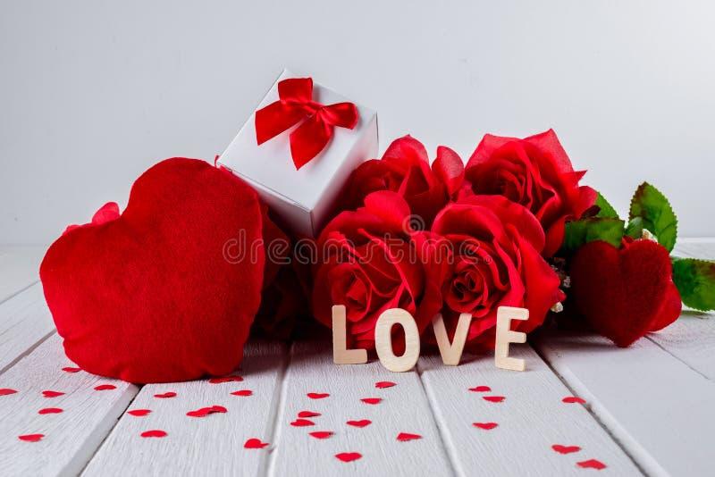Valentinbakgrund med den röda rosen, hjärtaform, gåvaask, träbokstavsord arkivfoto