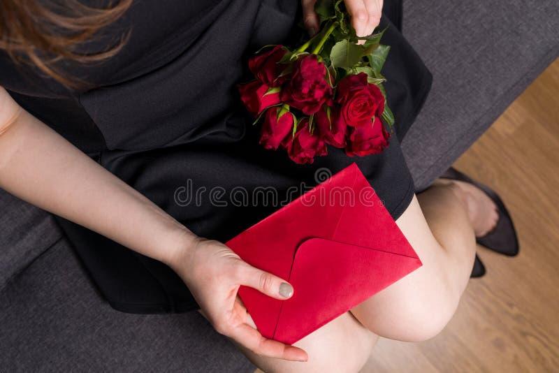 Valentindagöverraskning, härlig kvinna som rymmer röda rosor och det röda kuvertmeddelandet fotografering för bildbyråer