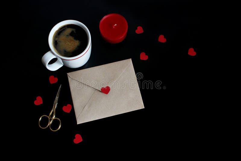 Valentindag eller bröllopmodellplats med koppen kaffe, kuvert, pappers- hjärtakonfetti, röd stearinljus, guld- sax royaltyfria bilder