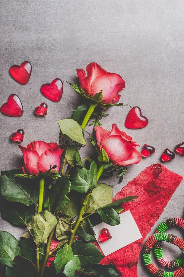 Valentindag, förälskelse eller datummärkningbegrepp Röda rosor samlar ihop med gåvaasken, hälsningkortet för tomt papper och hjär royaltyfri bild