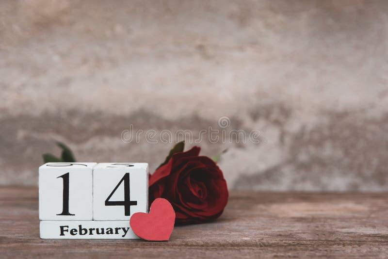 Valentindag med februari 14th Trävit kvarterkalender, röd ros och röd hjärta på trätabellbakgrund med kopieringsutrymme fotografering för bildbyråer