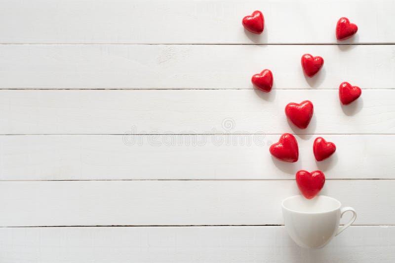 Valentindag och förälskelsebegrepp Röda hjärtor plaskar ut från koppen för vitt kaffe arkivfoto
