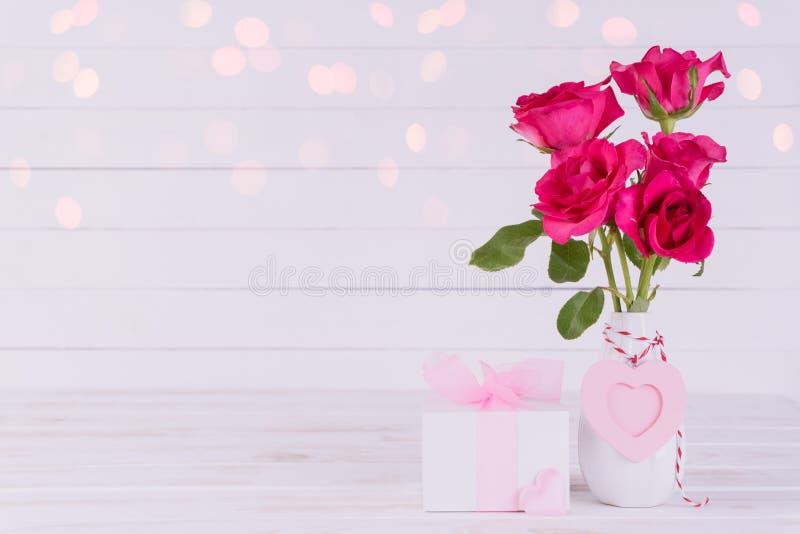 Valentindag och förälskelsebegrepp Rosa rosor i vas med trähjärta- och gåvaasken på vit träbakgrund royaltyfri bild