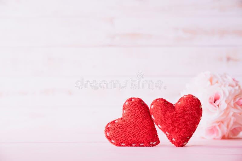 Valentindag och förälskelsebegrepp Två röda hjärtor med den rosa rosa blomman på vit träbakgrund royaltyfri fotografi