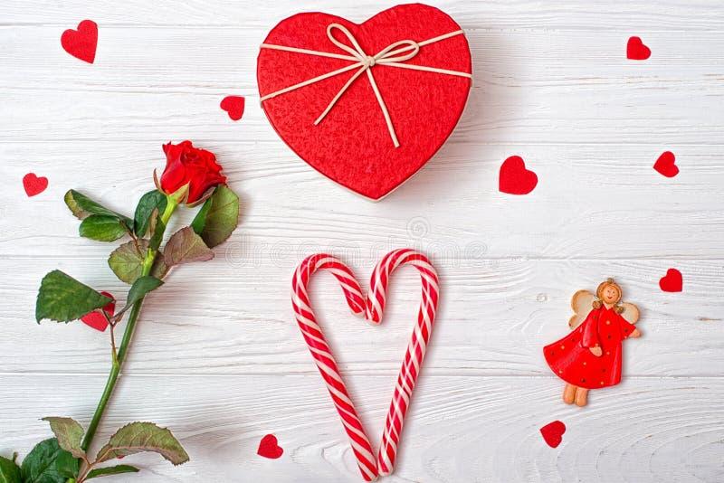 Valentindagbakgrund med en söt karamellhjärta, en röd ros och ängeln fotografering för bildbyråer